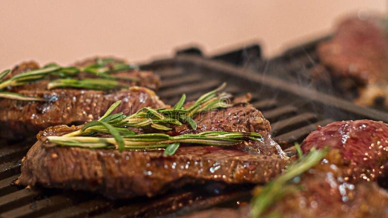 Amateur-chef& x27; s-Rauchen und saftige Rindfleischsteaks mit Rosmarin lizenzfreie stockfotos