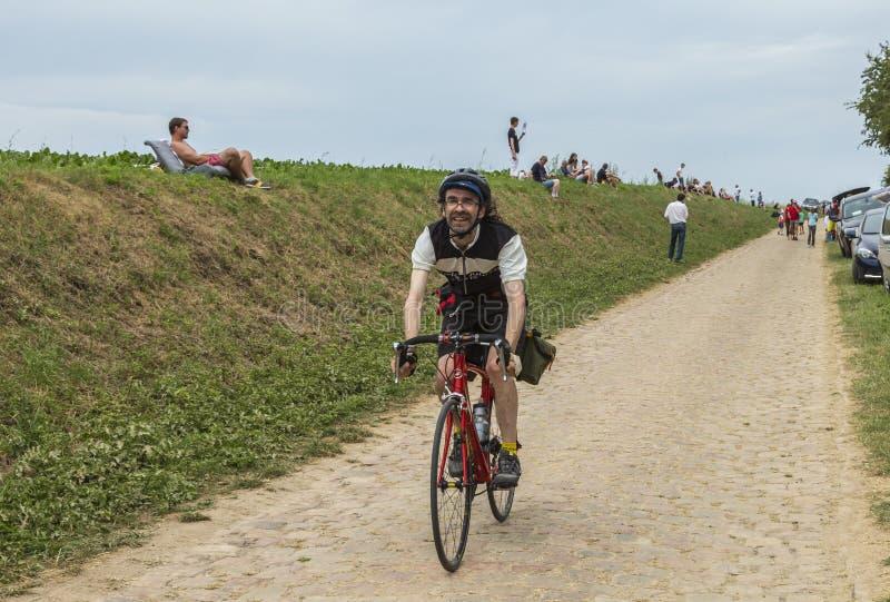 Amateur Cyclist Riding on a Cobblestone Road - Tour de France 2015 royalty free stock photo