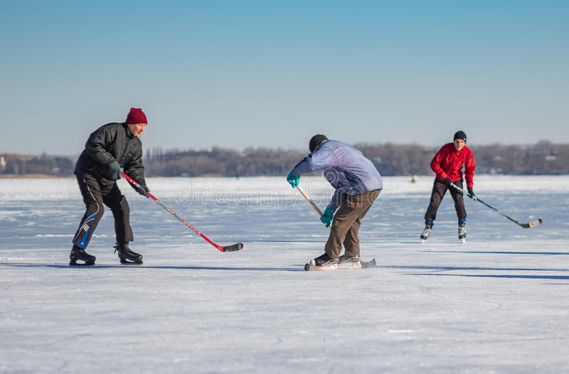 Amateur men playing hockey on a frozen river Dnepr in Ukraine at sunny weekend. Dnepr, Ukraine - January 22, 2017: Amateur men playing hockey on a frozen river royalty free stock photography