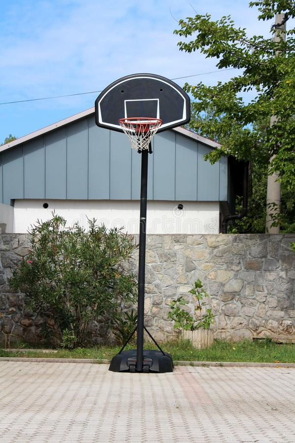Amateur metal and plastic basketball hoop mounted on stone tiles backyard in front of stone wall surrounded with trees and cloudy royalty free stock photography