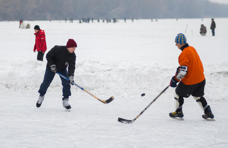 Amateur pair young and mature men playing hockey on a frozen river Dnepr in Ukraine royalty free stock photography