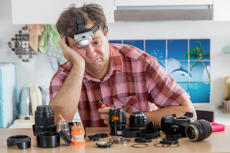 Amateur photographer is trying to repair his camera. Amateur photographer is trying to repair his lens. A hobby amateur cleans the device of a digital camera stock photos
