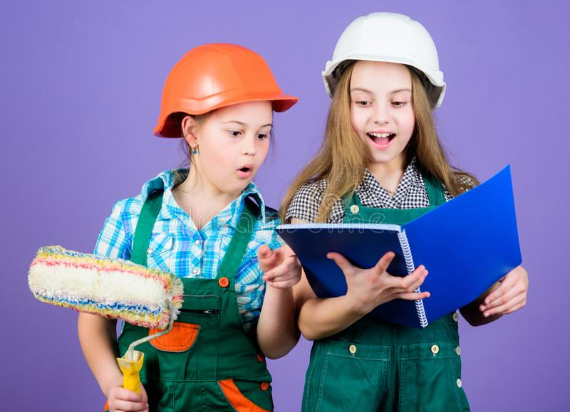 Amateur renovation. Sisters renovating home. Home improvement activities. Kids choosing paint colour for their new room. Kids girls planning renovation royalty free stock images