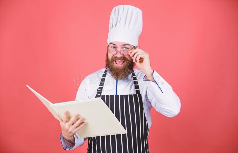 Amateurkok gelezen boekrecepten Culinair Kunstenconcept De mens leert recept probeer nieuw iets Het koken op mijn mening verbeter stock foto