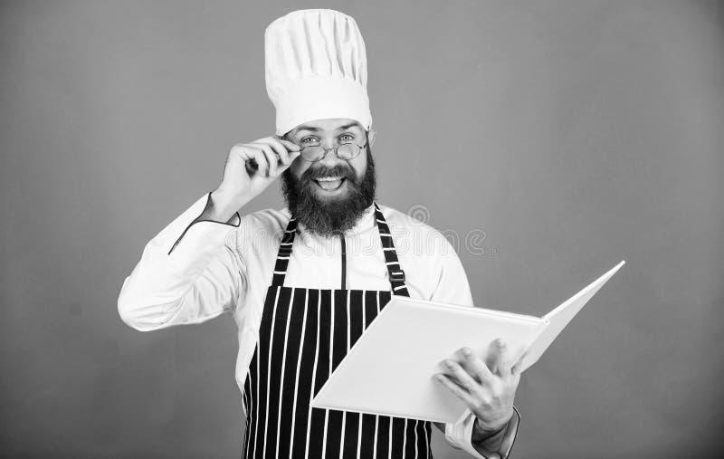 Amateurkok gelezen boekrecepten De mens leert recept probeer nieuw iets Het koken op mijn mening Verbeter het koken vaardigheid B stock fotografie