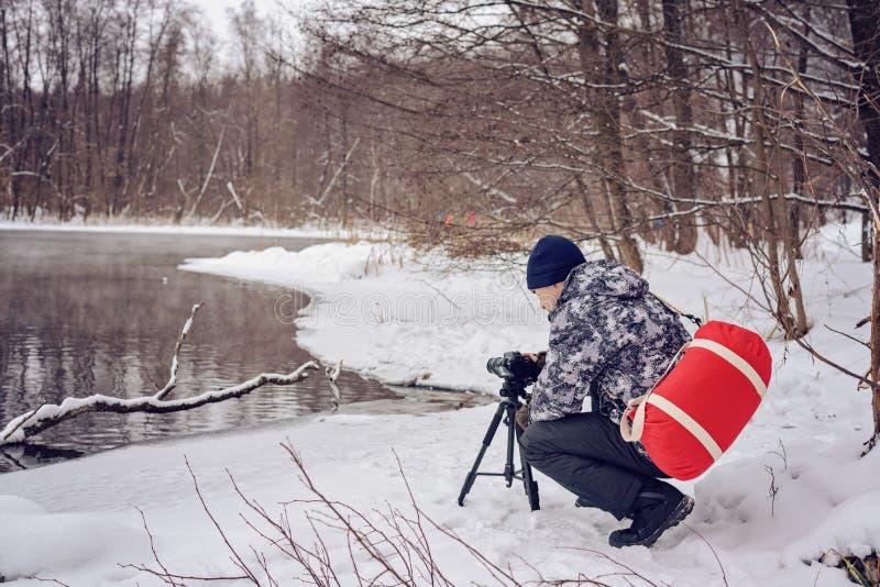 Amateurphotograph nimmt eine Winterlandschaft auf dem See im Waldkopienraum lizenzfreie stockbilder