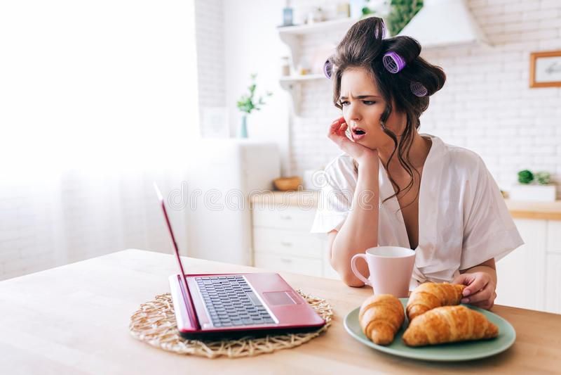 Amazed想知道在膝上型计算机的年轻女人神色 电影在厨房里 新月形面包和杯子在桌上的饮料 r 免版税库存照片