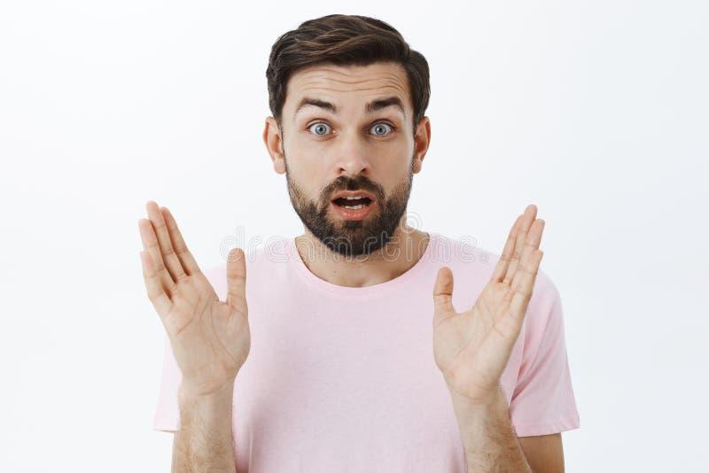 Amazed возбудило красивую мужскую модель с бородой и темным коротким стилем причесок показывая жестами с поднятыми ладонями раскр стоковое изображение