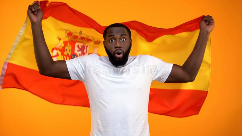 Amazed African-American sport fan holding Spain flag, cheering for victory stock images