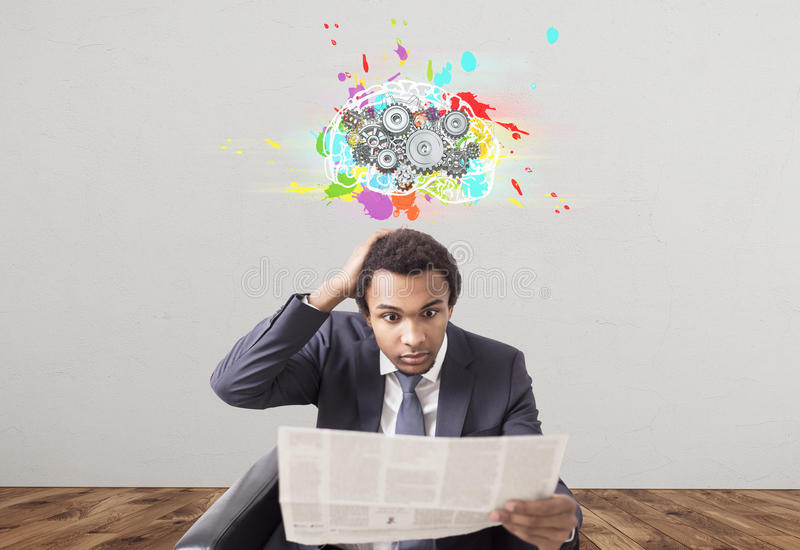 Amazed African businessman, newspaper, brain cogs. Portrait of a confused African American businessman in a suit reading a newspaper and sitting in an armchair royalty free stock photo