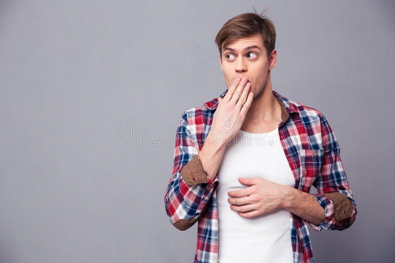 Amazed astonished man covered mouth by hand and feeling afraid stock photography