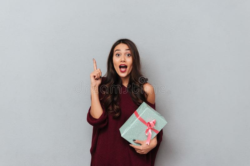 Amazed attractive brunette woman pointing with finger upward and. Holding present, isolated over gray background stock photo