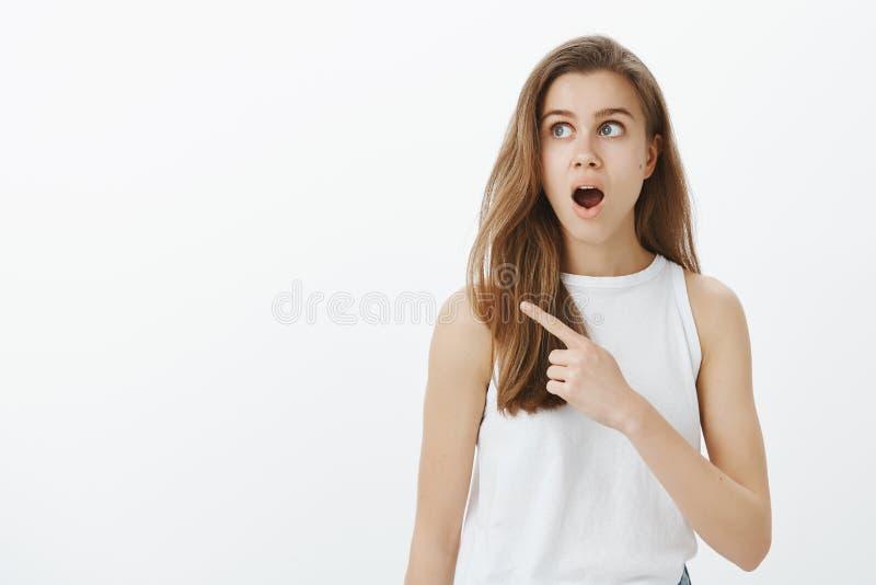 Amazed aturdiu a mulher atrativa com cabelo justo na camiseta de alças branca à moda, apontando e olhando o canto esquerdo superi foto de stock royalty free