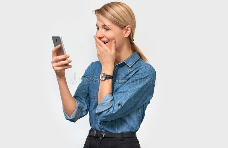 Amazed beautiful blonde woman, laughing and feeling happy to reading good news, wearing denim shirt, posing on white background stock photography