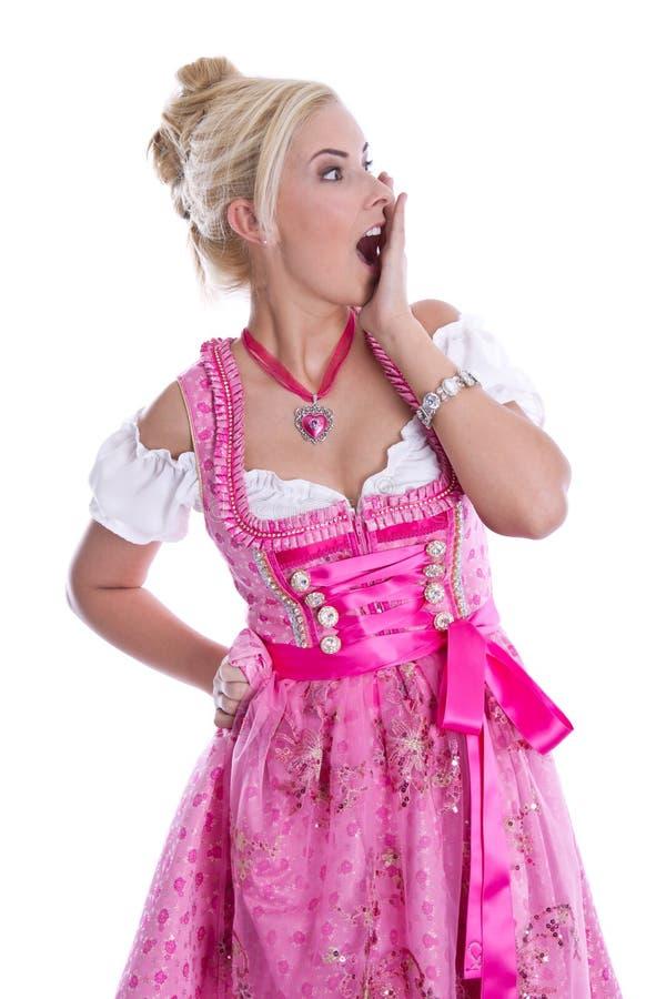 Amazed beautiful isolated bavarian woman wearing pink traditional dress. Amazed beautiful isolated bavarian woman wearing pink traditional dress over white stock photo