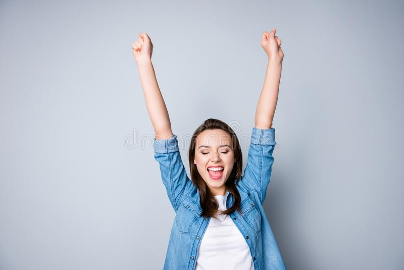 Amazed brunette young business woman in casual shirt is gesturing victory with her raised hands, she is shocked, extremely royalty free stock images