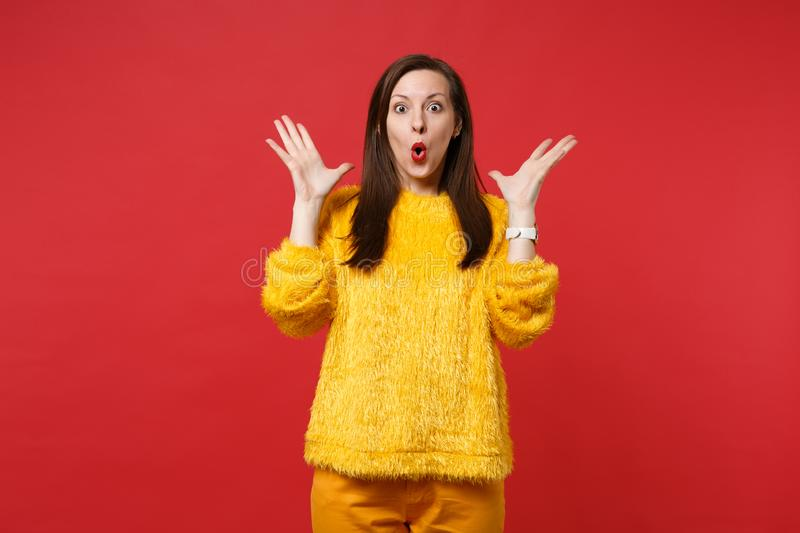 Amazed chocó a la mujer joven en el suéter amarillo de la piel que mantenía la boca las manos abiertas, de extensiones aisladas e imagen de archivo