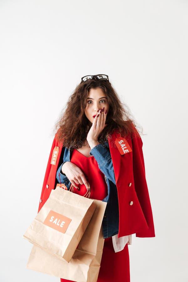 Amazed chocou a mulher da venda da compra que guarda os sacos de compras de papel imagem de stock