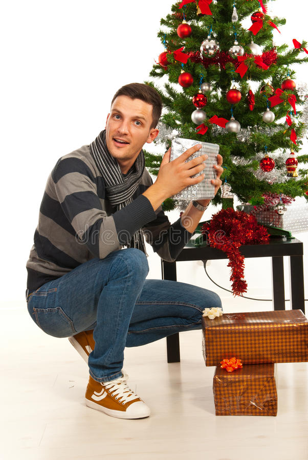 Amazed Christmas man with gift. Amazed Christmas man holding gift in front of tree stock images