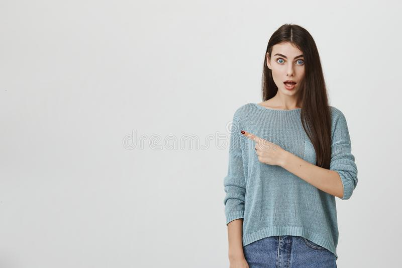 Amazed emotional european woman in blue sweater with popped eyes and opened in excitement mouth, pointing index fingers royalty free stock photos