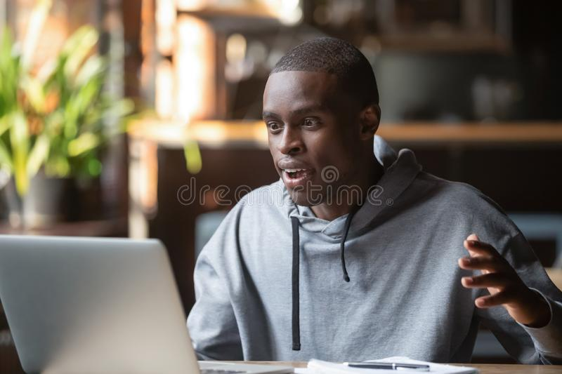 Amazed excited african man surprised by unexpected good news online. African millennial man sitting at table in cafe or office looking on computer screen feels royalty free stock images