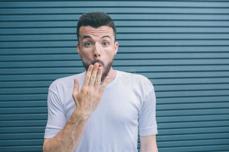 Amazed and excited guy is looking on camera. He is covering mouth with hand. Isolated on striped and blue background. royalty free stock photo