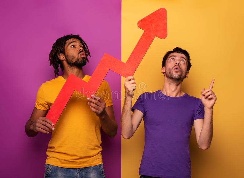 Amazed friends with funny face expression and red arrow statistic. Concept of growth, success, earn. stock image