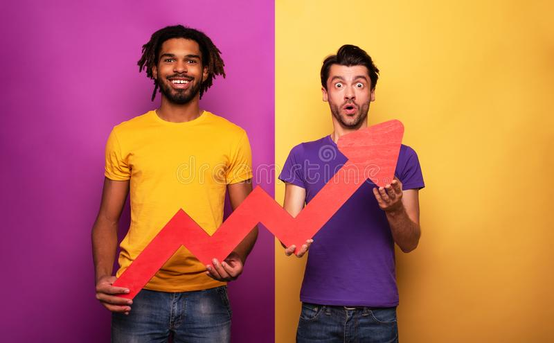 Amazed friends with funny face expression and red arrow statistic. Concept of growth, success, earn. stock photos