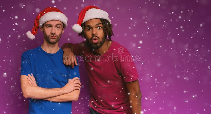 Amazed friends surprised by the arrival of Christmas. Purple background. Amazed friends surprised by the arrival of Christmas with hat. Purple background royalty free stock image