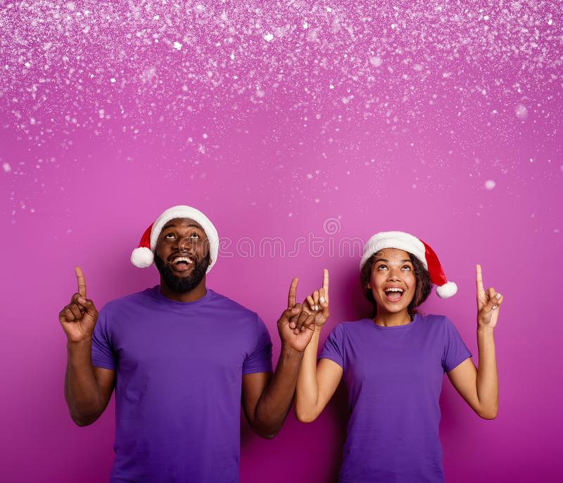 Amazed friends surprised by the arrival of Christmas. Purple background. Amazed friends surprised by the arrival of Christmas with hat. Purple background royalty free stock photos