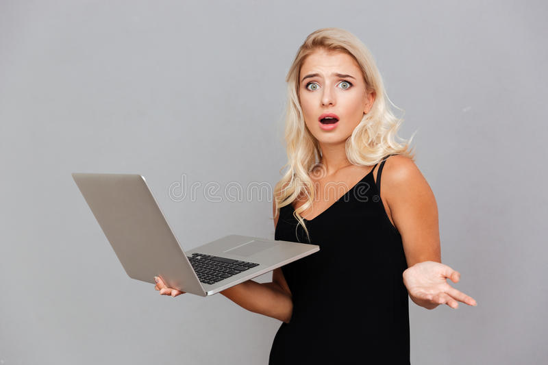 Amazed frustrated woman in black dress holding laptop. Over gray background stock photography