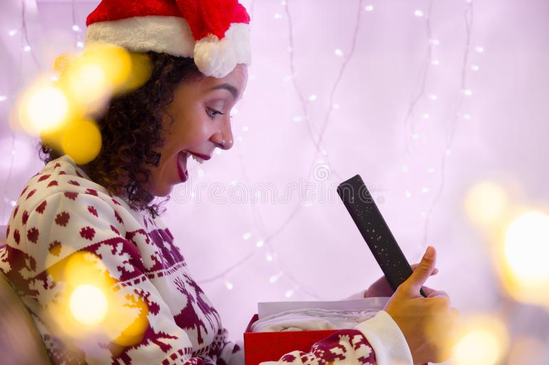 Amazed girl with christmas hat and seasonal sweater opens gift. Amazed Mixed race girl with christmas hat and seasonal sweater opens gift box at home. blurred royalty free stock photography
