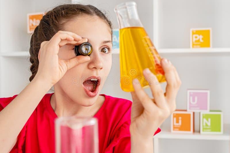 Amazed girl examining chemical liquid in flask stock photo