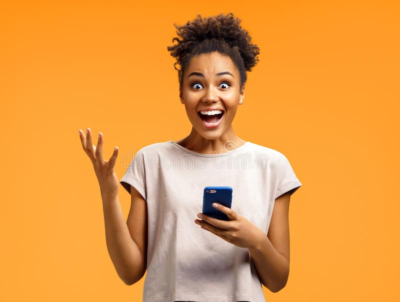Amazed girl holds smartphone, happy to receive notification, gestures actively from happiness. Photo of african american girl on orange background. Emotions royalty free stock images
