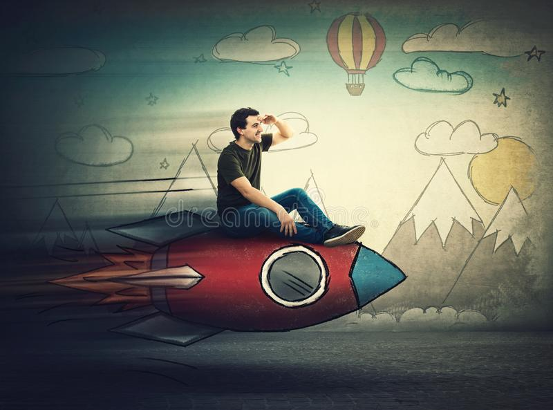 Amazed guy flying on a fast rocket looking hand to forehead looking far away for a vacation destination. Excited man searching for stock images