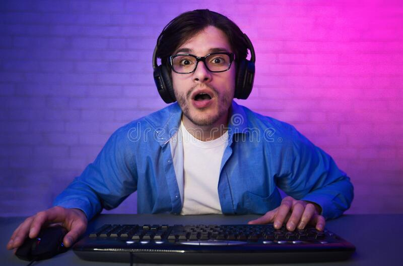 Amazed Guy Playing Computer Game Online Sitting At Home stock photography