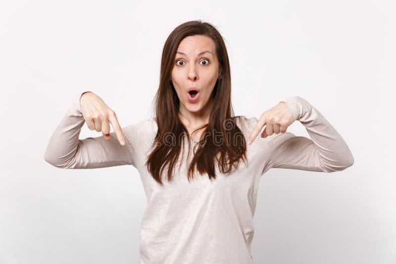 Amazed ha colpito la giovane donna in vestiti leggeri che tengono la bocca aperta, indicando i dito indice giù isolati sulla pare immagine stock