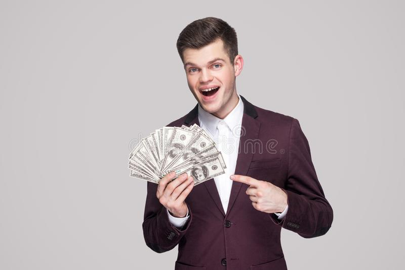 Amazed handsome brunette young businessman in classic violet coat standing, holding many dollars, pointing finger and looking royalty free stock photo