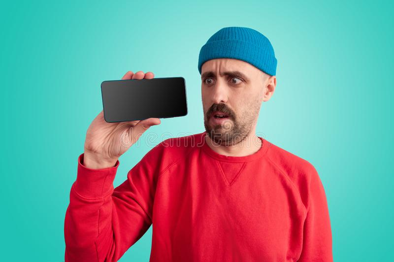 Amazed man looking at mobile phone in his hand royalty free stock image