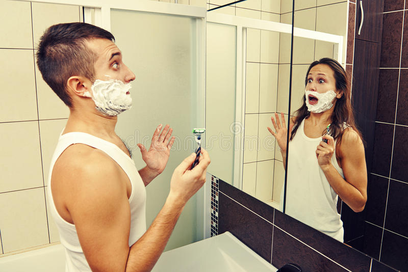 Amazed man shaving. Amazed men shaving and looking in the mirror stock images