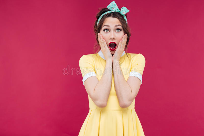 Amazed pinup girl in yellow dress standing with mouth opened royalty free stock photography