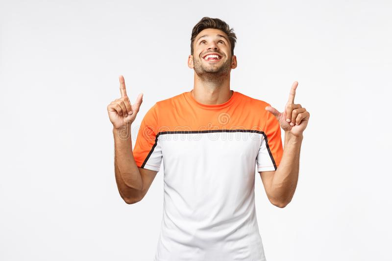 Amazed, pleased good-looking bearded man in sports t-shirt, raise head and pointing up astonished, smiling from stock photos