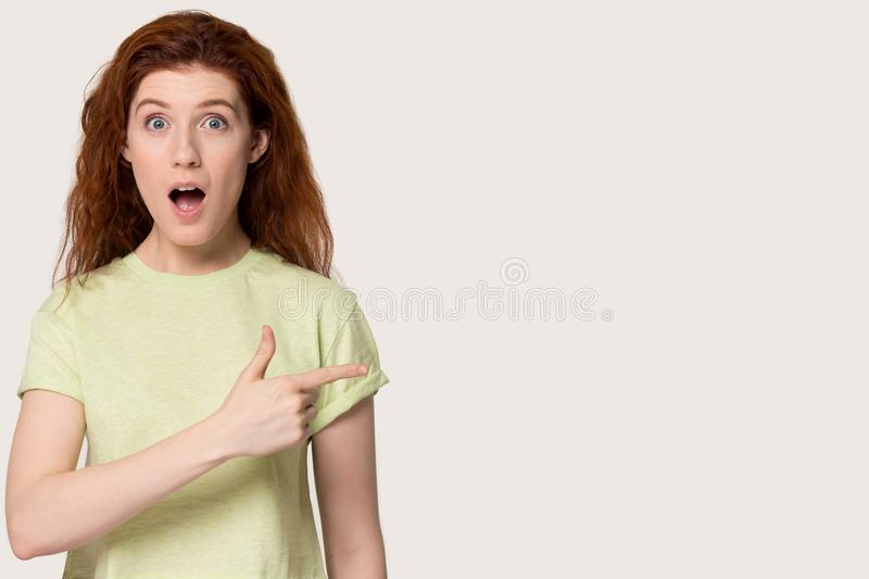 Amazed red-haired girl show at free copy space. Amazed redhead young woman in casual clothes isolated on grey studio background point at free copy space aside royalty free stock photos