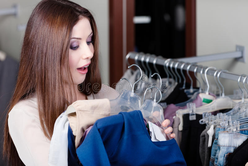Amazed with sale. Young woman is amazed with sale in this shop stock image