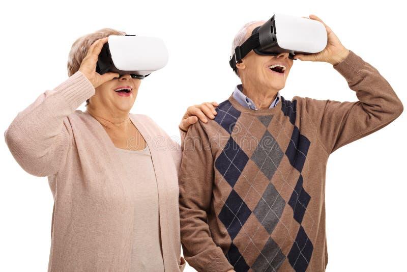 Amazed senior couple experiencing virtual reality. Isolated on white background royalty free stock photos