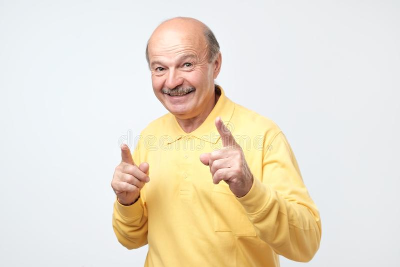 Amazed senior man has excited expression, index finger up, recieve good idea. For new project work. Happy pleased male isolated on white studio wall royalty free stock image