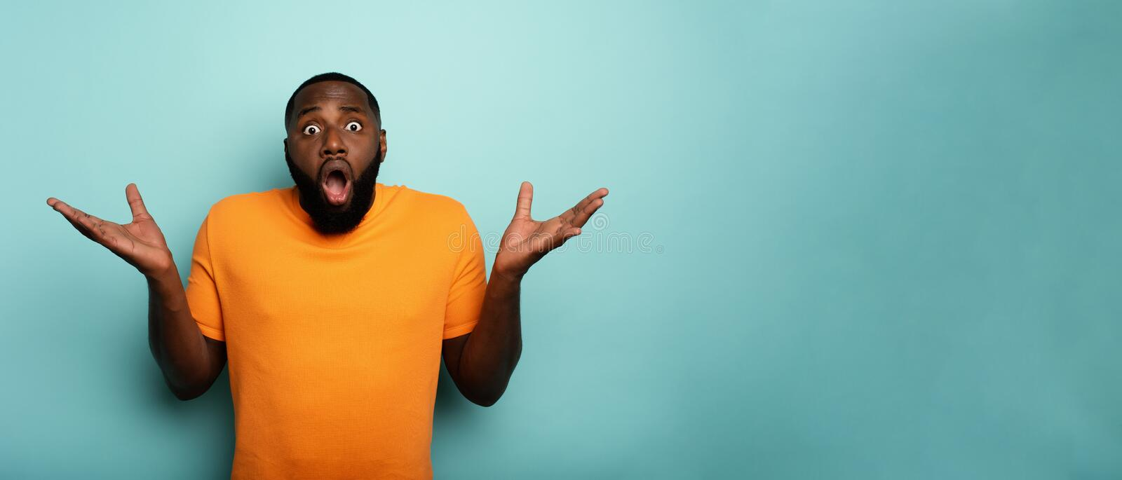 Amazed and shocked expression of a boy over cyan background. Amazed and shocked expression of a black boy over cyan background stock image