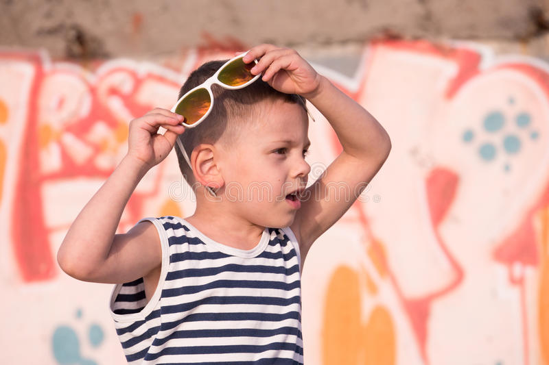 Amazed small boy with sunglasses and sailor shirt on graffiti wall background. Amazed little boy with white sunglasses and sailor stripes shirt on yellow and stock image