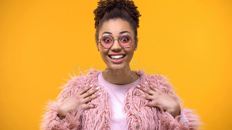 Amazed stylish female in pink eyeglasses looking camera, excitement expression stock image