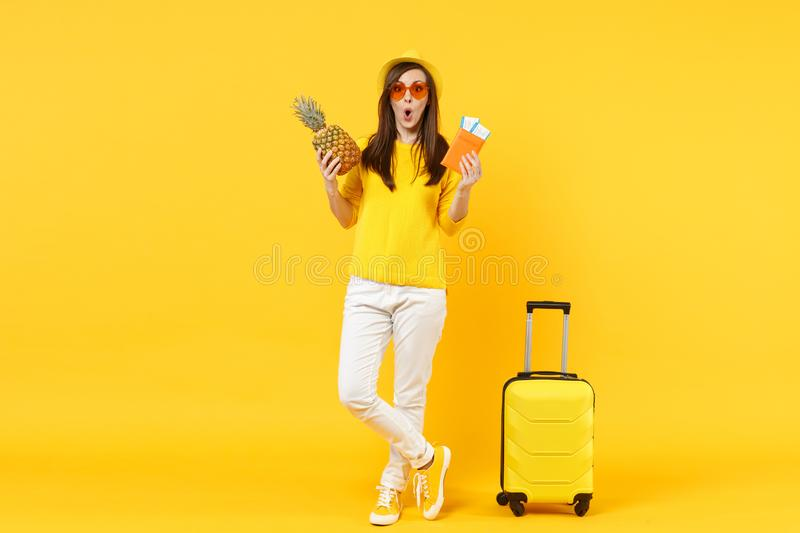Amazed traveler tourist woman in hat holding passport tickets, fresh pineapple fruit isolated on yellow orange. Background. Passenger traveling abroad on royalty free stock photos